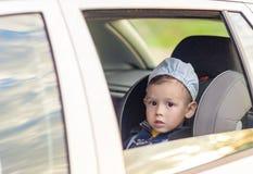 Safety Concept: Portrait Of Young Caucasian Happy Little Boy Sit Stock Photo