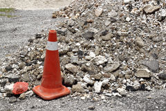Safety cone. An image of a safety cone near a pile of construction debris stock photo