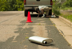 Safety cone and muffler on the side of the road Stock Photos