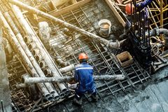 Safety construction workers. Construction workers wear protective clothing and yellow helmets, lifting steel pipes in construction sites in the capital royalty free stock image