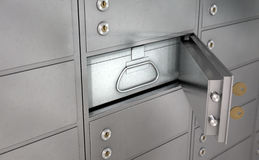Safety Deposit Boxes. A closeup of a wall of closed metal safety deposit boxes with one open revealing its contents inside Royalty Free Stock Image