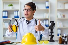 The safety doctor advising about noise cancelling headphones. Safety doctor advising about noise cancelling headphones royalty free stock photos
