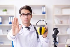 The safety doctor advising about noise cancelling headphones. Safety doctor advising about noise cancelling headphones stock images