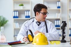 The safety doctor advising about noise cancelling headphones. Safety doctor advising about noise cancelling headphones royalty free stock images