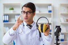 The safety doctor advising about noise cancelling headphones. Safety doctor advising about noise cancelling headphones stock photo