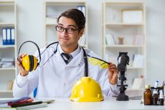 The safety doctor advising about noise cancelling headphones. Safety doctor advising about noise cancelling headphones royalty free stock image