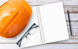 Safety Engineer Helmet with wood background. Safety Engineer Helmet,notebook,glasses and pencil on white wood background Stock Image