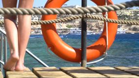 Safety equipment, Life buoy or rescue buoy on the wooden pier at the beach. 120fps stock footage