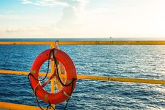Safety equipment, Life buoy or rescue buoy hanging on handrail with sea sky background in sun set time Stock Photo