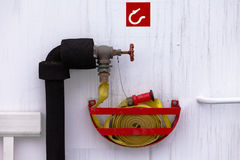 Fire hose on water outlet ready for fire emergency. Safety equipment rolled up yellow fire hose attached to water hydrant ready to be used in an fire emergency Royalty Free Stock Image