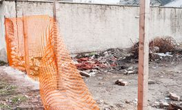 Construction site safety orange net or fence around of remains of hurricane or earthquake disaster damage on ruined old house sele stock image