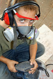 Safety First. Boy wearing safety goggle, earmuffs and respirator, looks up as he sands a project Stock Images
