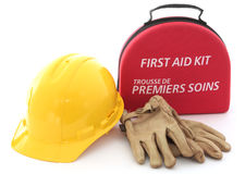 Safety First. A first-aid kit, hardhat, and gloves spell out the need for safety in the workplace Royalty Free Stock Image