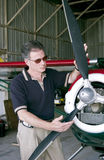 Safety First. A man standing with his hands on the propeller of a small single engine plane Royalty Free Stock Image