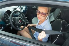 Safety first. Beautiful blonde caucasian lady fastening car seat belt. Safety first. Beautiful blonde casual caucasian woman wearing sunnglasses, blue shirt and stock image