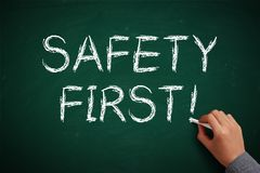 Safety First. Hand with white chalk writing 'Safety First' on chalkboard Stock Photography