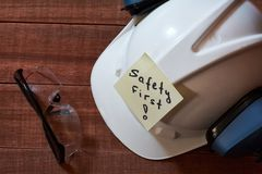 Safety first note one yellow piece of paper stuck on wooden background with full set of personal protective equipment: helmet, saf. Et glasses and ear protection stock photography