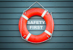 Safety first. Red lifebuoy hanging on blue wall Stock Photography
