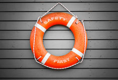 Safety first. Red lifebuoy hanging on gray wall Stock Photos