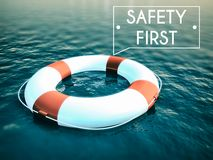 Safety First sign lifebuoy on rough water waves Stock Photo