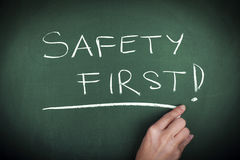 SAFETY FIRST. Woman hand writing SAFETY FIRST note on green blackboard Royalty Free Stock Photography