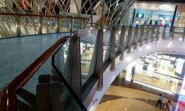 Safety Glass handrail in big shopping mall. 20mm thick tempered glass handrail and protected with wooden handrail in first floor level in an big shopping mall royalty free stock images