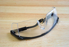 Safety glasses on a wood table top Stock Photo