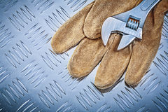 Safety gloves adjustable spanner on grooved metal sheet construc. Tion concept Royalty Free Stock Images
