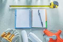Safety gloves construction drawings tape measure notepad pen on Royalty Free Stock Image
