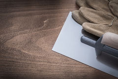 Safety gloves and glazed plastering trowel top view construction Royalty Free Stock Photos