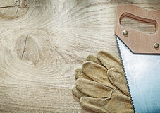 Safety gloves hacksaw on wooden board construction concept Royalty Free Stock Photo