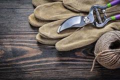 Safety gloves hank of rope secateurs on vintage wooden board gar Stock Image