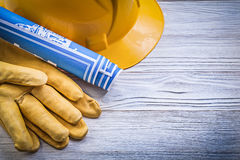 Safety gloves hard hat blue engineering drawings on wooden board Royalty Free Stock Photography