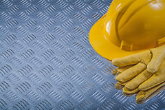 Safety gloves hard hat on channeled metal sheet construction con Royalty Free Stock Photos