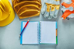 Safety gloves hard hat notepad pencil toolbelt tape measure on c. Oncrete background Royalty Free Stock Photo
