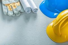 Safety gloves hard hats blueprints on concrete background Stock Photo