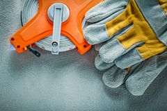 Safety gloves measuring tape on concrete background Royalty Free Stock Photo