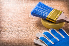 Safety gloves paint brush and duct tape on wooden Royalty Free Stock Photography