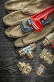 Safety gloves plumbing pipe wrench fittings water valve on woode. N board Royalty Free Stock Photos