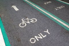 Safety green bicycle lane on road. Bicycle sign stock photos