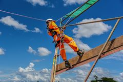 Safety haness. Workers up high with safety equipment and safety belts, construction workers wearing safety harness belt high place on blue sky background Royalty Free Stock Images