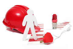 Safety in a hazardous workplace. Wooden figure standing next to warning light,hard hat , chevron and electrical cord with plug stock images