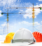 Safety helmet against sketching of building construction with li. Fting crane use for civil engineering ,land and urban development topic Royalty Free Stock Photo