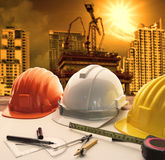 Safety helmet on architect ,engineer working table with modern b. Uilding and crane construction background use for construction business and civil engineering Stock Photography
