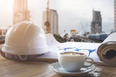 Safety helmet blue print plan and cup of coffee on engineer work stock photography