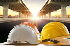 Safety helmet on civil engineering working table against bridge. Construction in urban scene Royalty Free Stock Photo