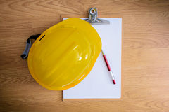 Safety helmet, clipboard, notebook, pen on wooden table Royalty Free Stock Images