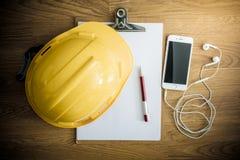 Safety helmet, clipboard, notebook, pen on wooden table Stock Photos