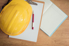 Safety helmet, clipboard, notebook, pen on wooden table Royalty Free Stock Photo