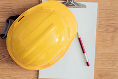 Safety helmet, clipboard, notebook, pen on wooden table Royalty Free Stock Photography